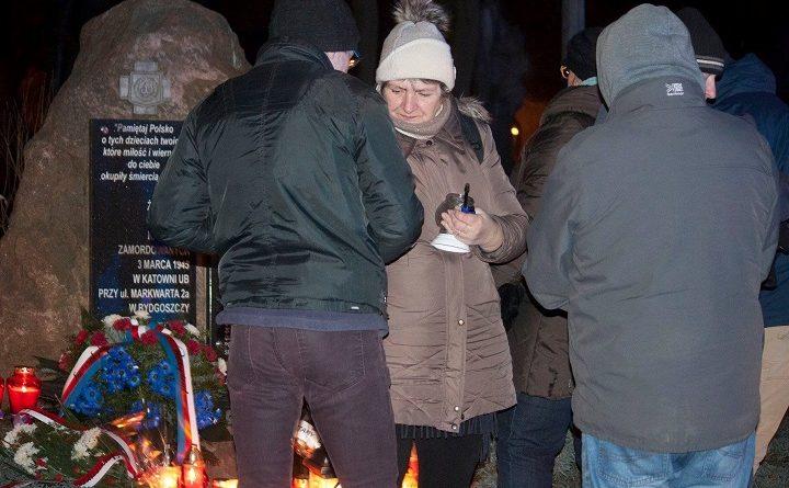 Obywatele RP zapalają znicz pod tablicą upamiętniającą ppor. Leszka Białego